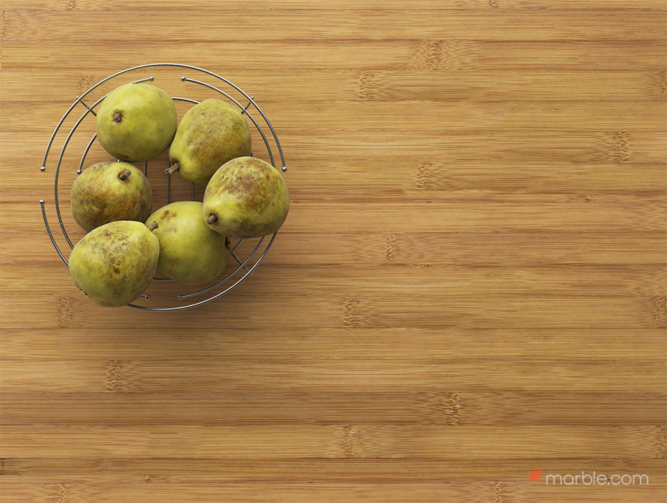 Pears in metal bowl on bamboo countertop