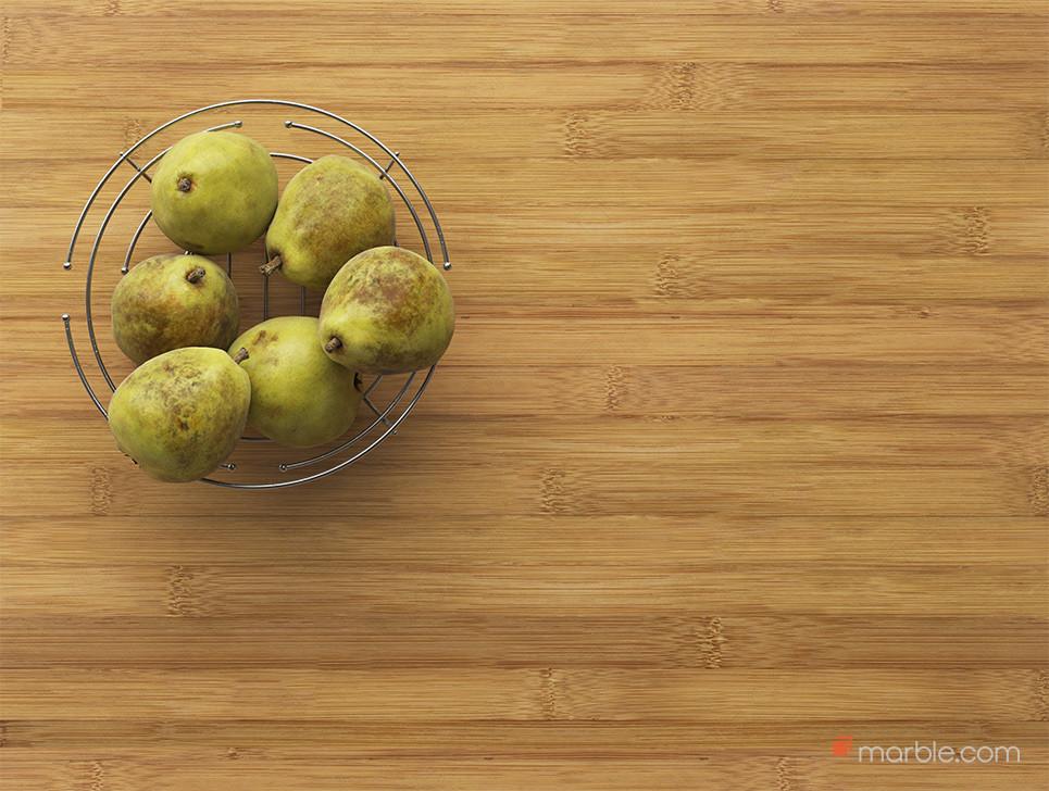 Pears in metal bowl on bamboo countertop